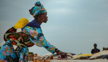 A woman carrying a baby on her back sells fish in Yoff, Senegal