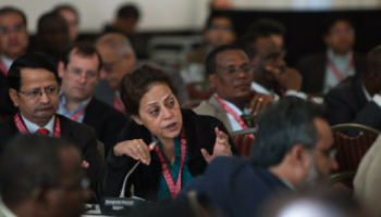 Woman leaning over and talking into a mic in a conference