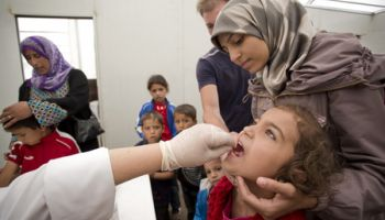 Fatima, a Syrian refugee as her child vaccinated