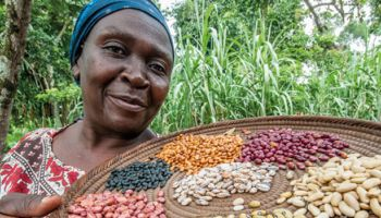 a woman holding a try of different types of beans