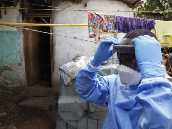 A worker for the ministry of health prepares to enter a house with protective clothing